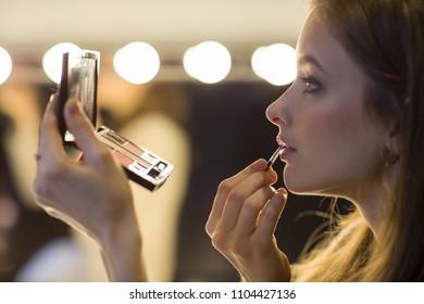 Beautiful slim and young woman prepares, she uses lipstick, and makeup set