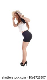 Beautiful slim young woman standing in profile with a straw hat and