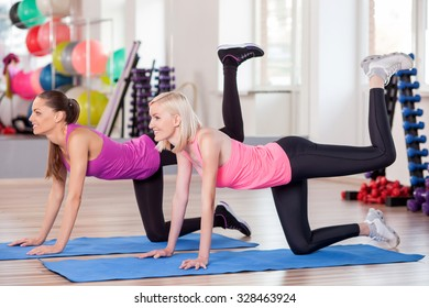 Beautiful slim young women are doing exercises in gym. They are kneeling on carpets and stretching legs up. The ladies are smiling