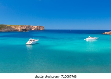 Beautiful small bay with clear turquoise water and speed boats, Menorca island, Balearic islands, Spain.