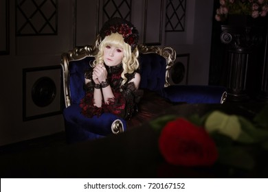 A beautiful, small, blond girl, sits on an expensive carved sofa in a red lush old dress. The woman is the vampire Claudia. A princess. japanese style lolita, cosplay cute. Street fashion.