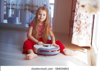 Beautiful small blonde girl playing with robot vacuum cleaner at home.