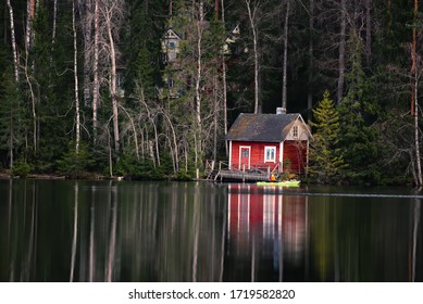 Beautiful small cabin in the beach of the lake in Finnish countryside. Front of the cabin canoeist sit on the canoe. Lake is calm.