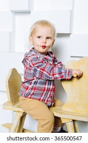 Beautiful small child riding on the toy horse. Happy candid emotions. Studio shot.