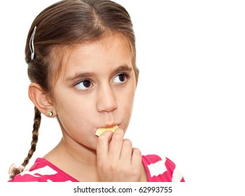 A beautiful small girl with braided hair eating crackers isolated on a white background