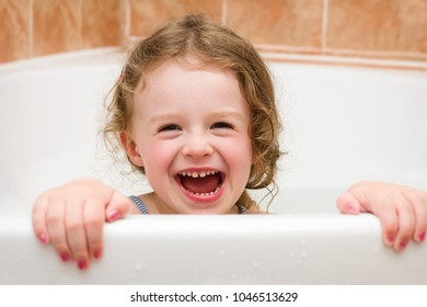 Beautiful small girl laughing in the bathroom