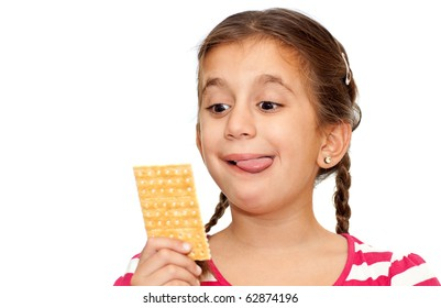 Beautiful small girl looking at a cracker with a funny face isolated on a white background