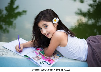 Beautiful small girl lying facedown barefoot by the garden pool, smiling, looking to camera and drawing on sketch book with pencil, red bowl with pencils by the pool on the ground, back to school