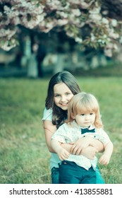 Beautiful small girl with smiling face holding little brother on hands on green grass in spring with pink blossom