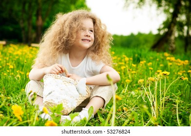beautiful small girl smiling and sitting on flower field in green grass with basket in hands