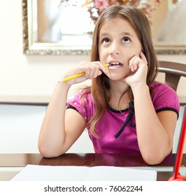 Beautiful small girl thinking while working on her school project at home