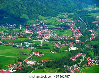 Beautiful small green town in the alps from above
