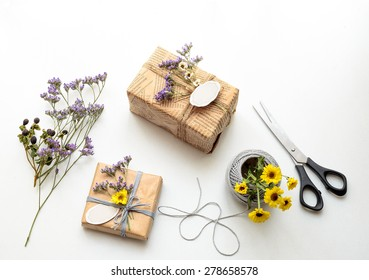 Beautiful small handmade gift box (package) with blank gift tag, with flowers and decorative rope on white background. Vintage Style.