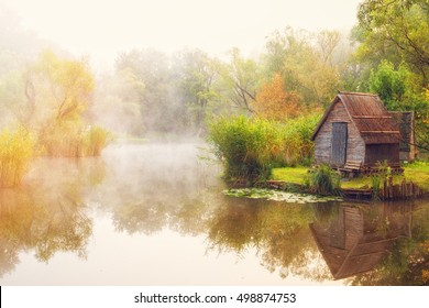 Beautiful small hut on the shore of small pond engulfed in fog