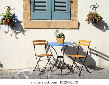 beautiful small iron chairs and a table on sidewalk in Cyprus