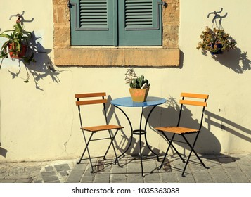 beautiful small iron chairs and a table on sidewalk in Cyprus. Toned image