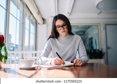 Beautiful smart bussinesswoman in stylish eyeglasses creating doing accountancy organisation work while sitting at coffee shop, young clever female student writing homework in notebook at cafeteria
