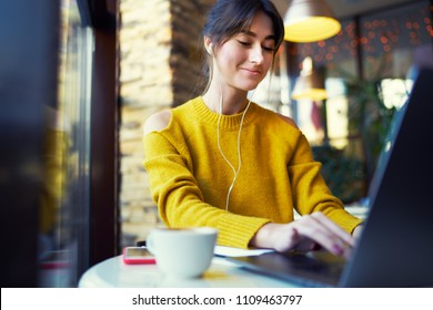 Beautiful smart girl web designer working on site with netbook in cafe. skilled copywriter making notes doing remote job on netbook concentrated on task, smiling and enjoying cool music in her playlis