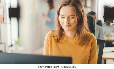 Beautiful and Smart Red Haired Female Specialist Sitting at Her Desk Works on a Desktop Computer. Bright and Modern Open Space Office with Stylish Ergonomic Furniture for Talented Creative People