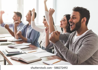 Beautiful smart students are raising hands in fists and smiling while sitting at the class