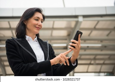 beautiful smile American senior business woman, 40 to 50 years old, brows and play smart or mobile phone to check project news with modern building background. Happy Fintech female work outside office