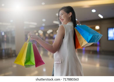 Beautiful smile girl holding colorful shopping bag and credit card