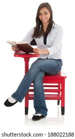 Beautiful smile on a teenage female student seated at a red school desk and reading a book. Studio shot, isolated on white background. Model is mixed ethnicity, part Asian and part Caucasian.