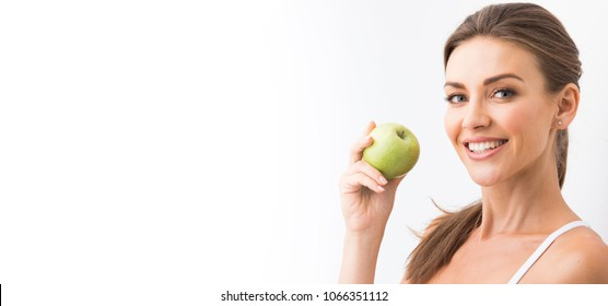 Beautiful smile, white strong teeth. Head and shoulders of young woman with snow-white toothy smile holding green apple, teethcare.