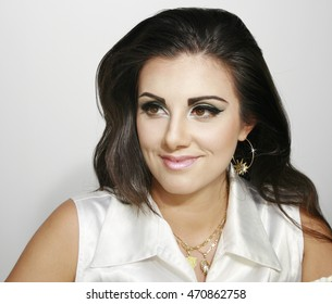 Beautiful smiley girl with makeup and earring, long dark hair