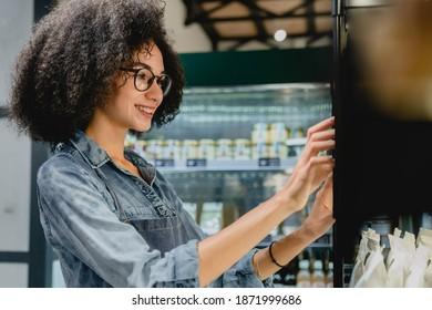 Beautiful smiling 20s female barista using vending machine in cosy coffee shop