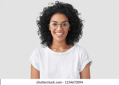 Beautiful smiling African American female with crisp hair, broad smile, shows white teeth, wears casual t shirt and spectacles, stands over studio wall rejoices having day off. Woman journalist indoor