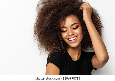 Beautiful smiling african american woman touching her afro hairstyle isolated on white background