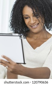 Beautiful smiling African American woman using her tablet computer.