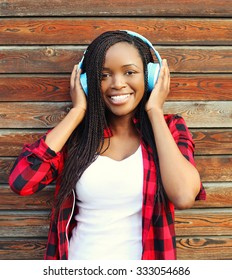Beautiful smiling african woman with headphones listens to music and having fun in city over wooden background