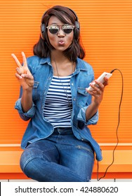Beautiful smiling african woman with headphones listens to music over orange background.  Fashion woman in sunglasses outdoor.