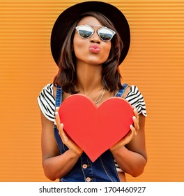 Beautiful smiling african woman holding a red heart. Fashion portrait stylish pretty woman in sunglasses outdoor.