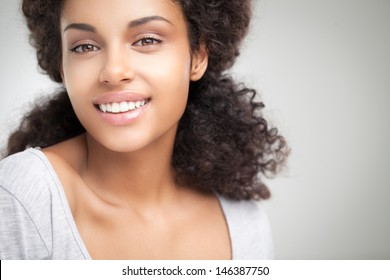 Beautiful smiling African woman posing against a gray background.