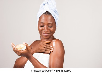 beautiful smiling african woman putting ointment on her body after her bath.