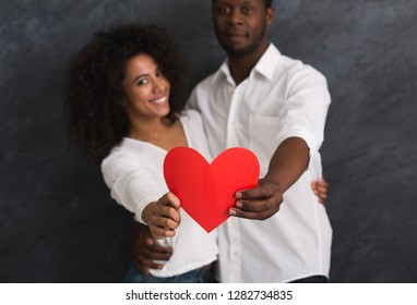 Beautiful smiling afro-american couple holding a big red paper heart on dark background. Happy Valentine concept