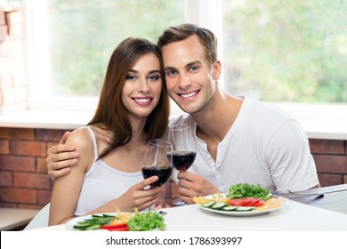 Beautiful smiling amorous couple drinking red wine, at home. Portrait image of caucasian models with redwine glasses in love concept. Happy man and woman together indoors.