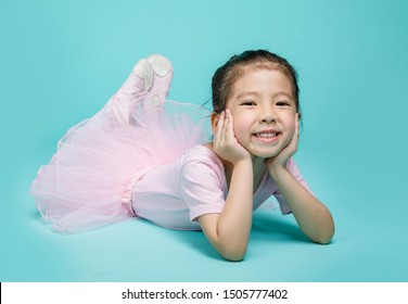 Beautiful smiling Asian little girl in a pink suit is dancing a ballet at school, studio shot isolated on colorful blue background