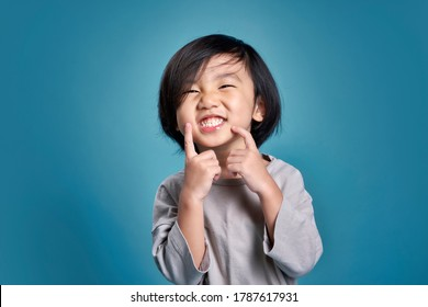 Beautiful smiling asian little kid show his teeth. Empty space in studio shot isolated on colorful blue background. Education concept for school.