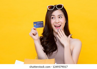 Beautiful smiling Asian woman carrying shopping bags showing credit card in hand studio shot isolated on colorful yellow background