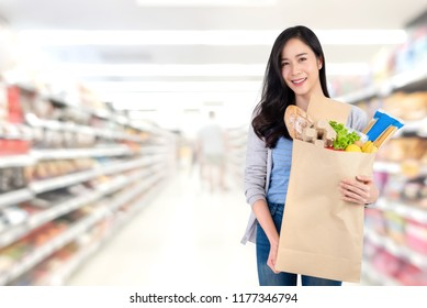 Beautiful smiling Asian woman holding paper shopping bag full of food and groceries in supermarket