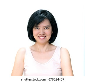 Beautiful smiling Asian women with clean skin, natural make-up, short black hair and white teeth isolated on white background. Middle aged woman wearing beige dress, image for skin and healthy concept