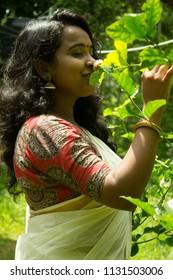 Beautiful smiling Asian/Indian/Kerala/ girl in traditional set saree and kalamkari blouse smells jasmine flower