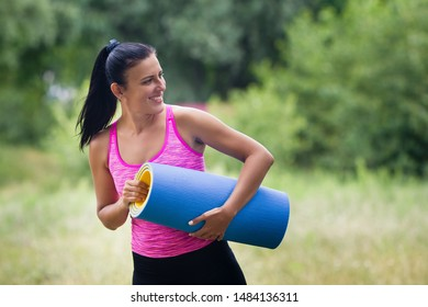 beautiful smiling athletic brunette girl in a pink tank top and black leggings in a park with a koremat in her hands looks back