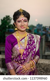Beautiful smiling Bengali Indian bride dressed in saree and jewelry posing on rooftop with setting sun on the background Indian lifestyle