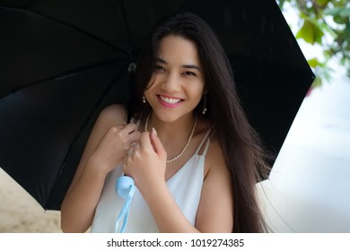 Beautiful smiling biracial Asian Caucasian woman or teen girl holding umbrella in rain