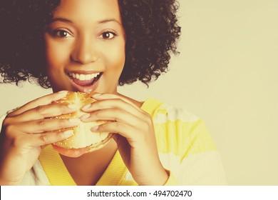 Beautiful smiling black woman eating food
